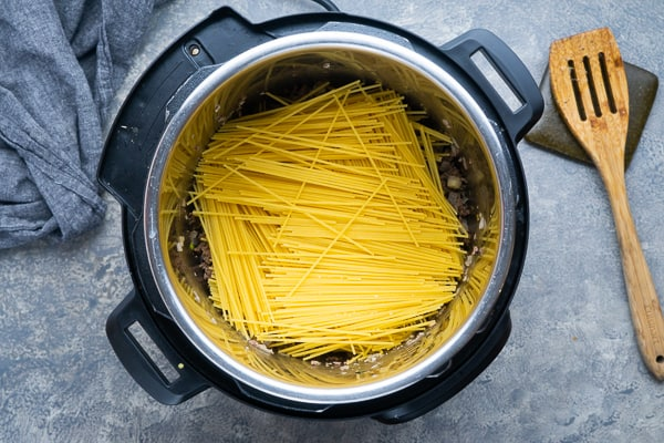 uncooked spaghetti noodles stacked on ground beef in instant pot