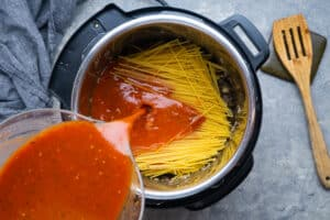spaghetti sauce being poured over spaghetti noodles in the instant pot