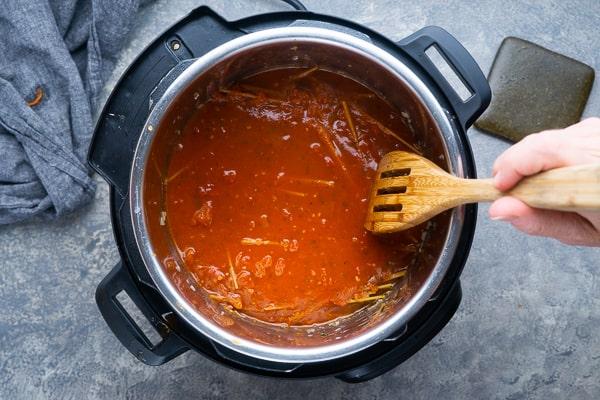 wooden utensil presses spaghetti noodles under spaghetti sauce in the instant pot