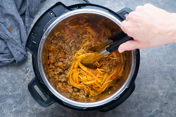 spaghetti and meat sauce being stirred with tongs in the instant pot