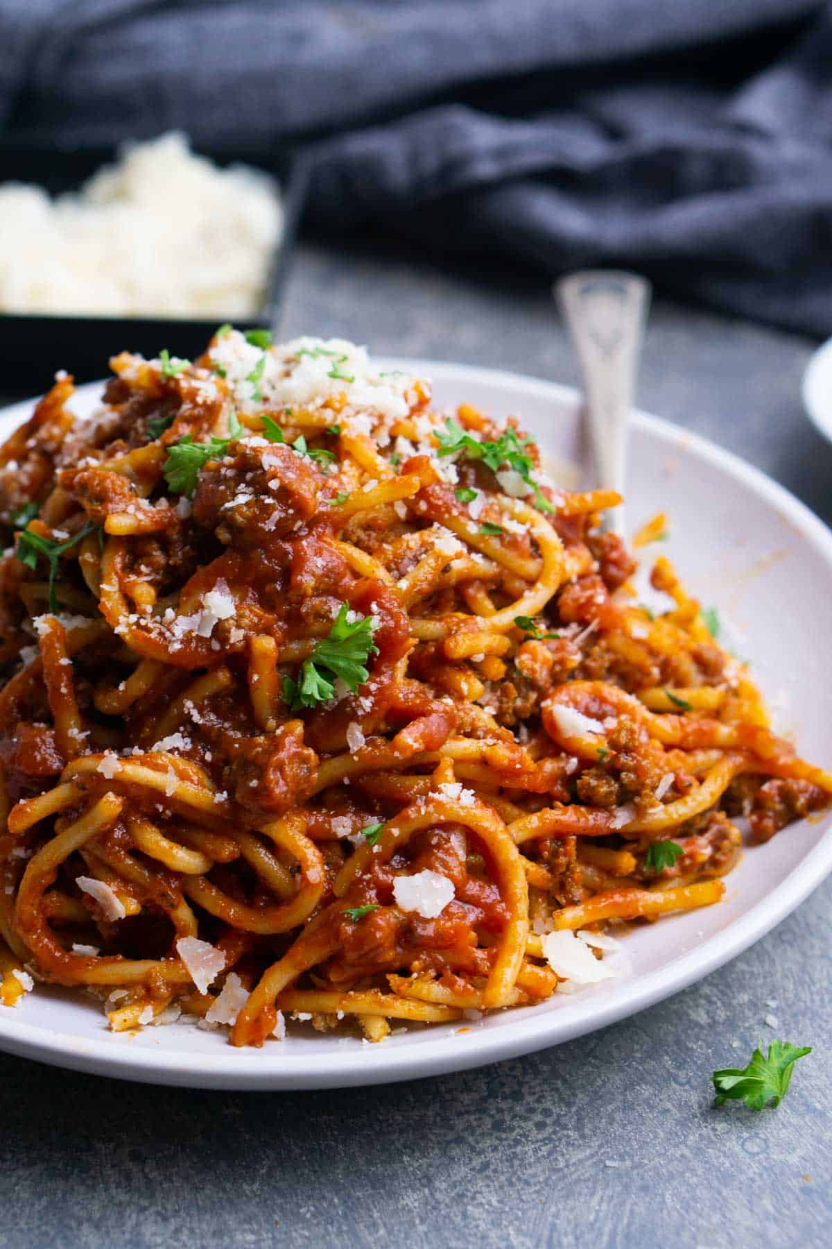 spaghetti and meat sauce on white plate with fork next to parmesan cheese