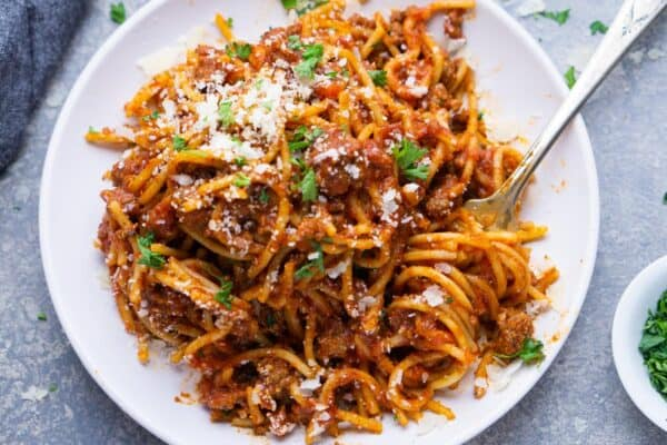 spaghetti and meat sauce on white plate with fork