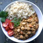 lentil chickpea curry, rice, tomatoes, and cilantro in white bowl on blue background