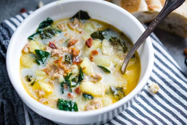 zuppa toscana with spoon in white bowl on gray striped linen with baguette