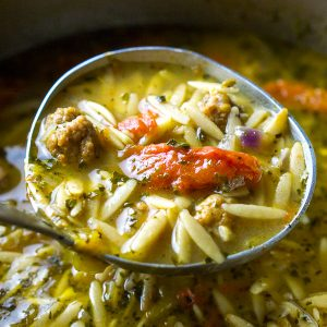 Italian sausage soup with orzo in soup ladle over soup pot