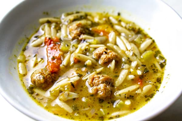 Italian sausage soup with orzo and white bowl