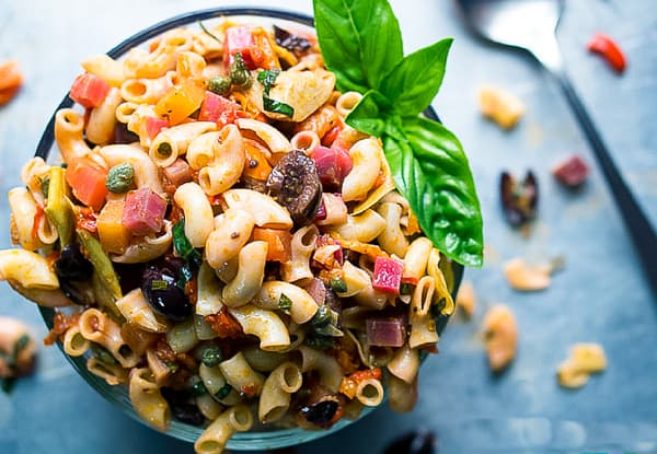Italian Vegan Pasta Salad in glass bowl on blue background