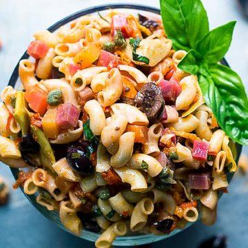 Italian Vegan Pasta Salad in glass bowl on blue background