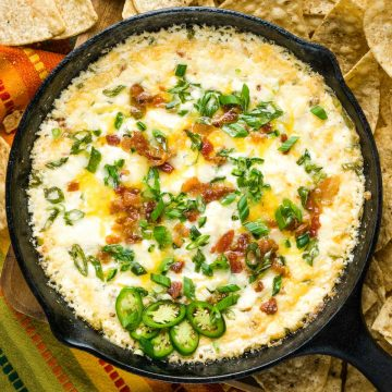 baked jalapeno popper dip in iron skillet surrounded by tortilla chips