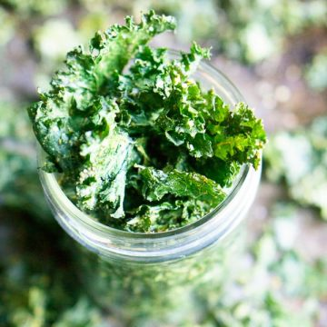 kale chips in glass jar on sheet pan with kale chips scattered
