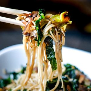 chopsticks with kale sesame noodles over white bowl