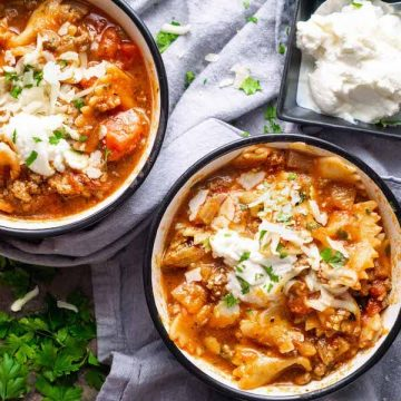 lasagna soup in ceramic cups on blue linen with ricotta cheese and parsley garnish