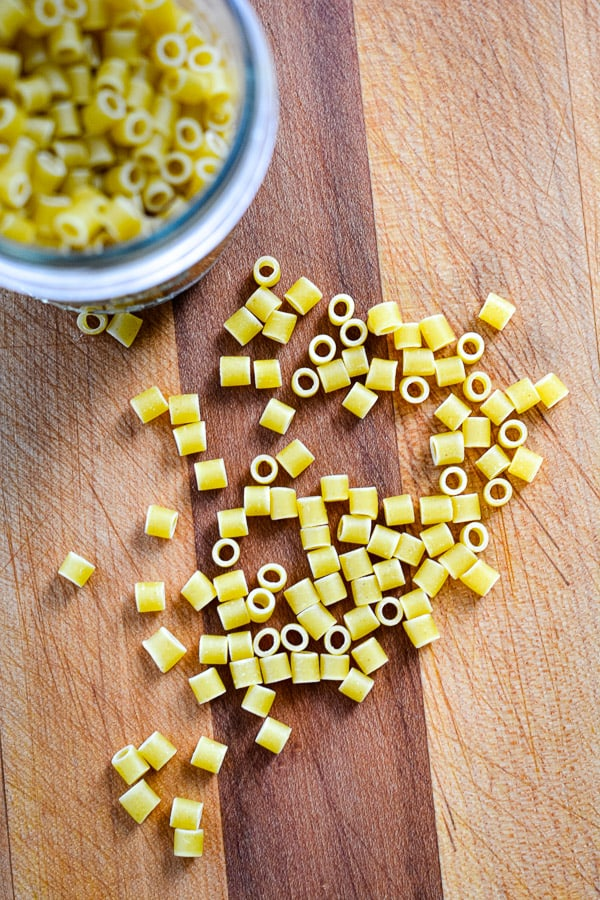 uncooked short cut macaroni pasta scattered on wood cutting board and piled in glass jar