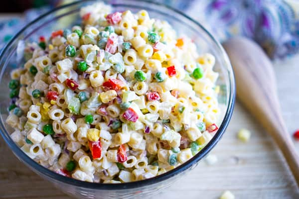 Macaroni salad in glass bowl on beige table with colorful linen and wooden spoon