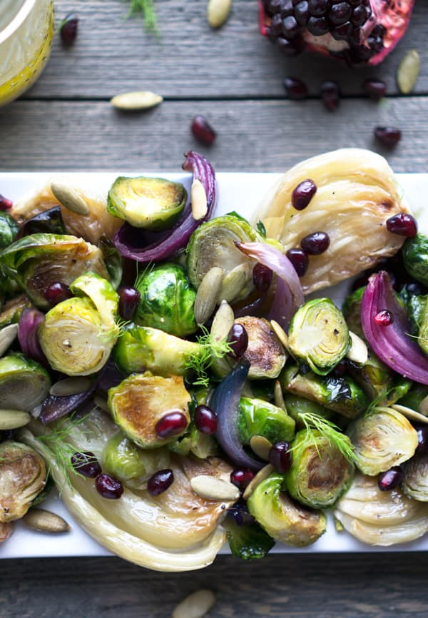 Roasted Brussels sprouts, red onion, fennel, pomegranate, and pepitas on white plate on gray background