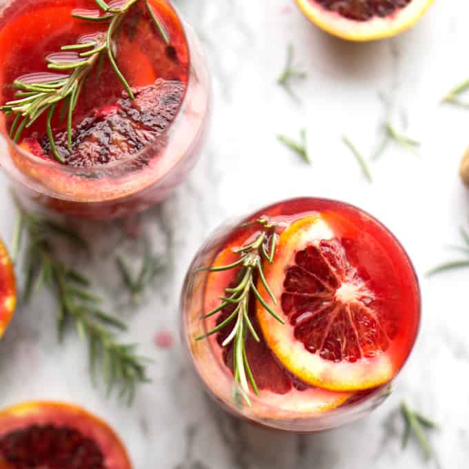 overhead view of blood orange mimosa garnished with rosemary sprig and blood orange slices in wine glass on marble background