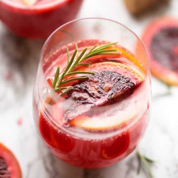 blood orange mimosa garnished with rosemary sprig and blood orange slices in wine glass on marble background