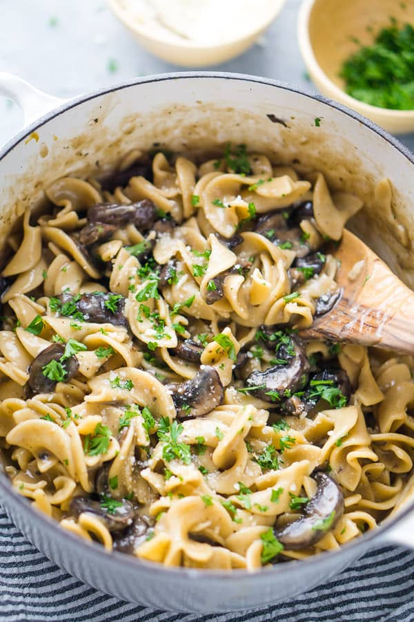 Mushroom stroganoff in white Dutch oven with wooden spoon