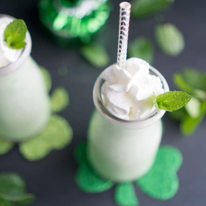 shamrock shake in glass bottles with straw, whipped cream, and mint leaf garnish next to St Patrick's Day decorations