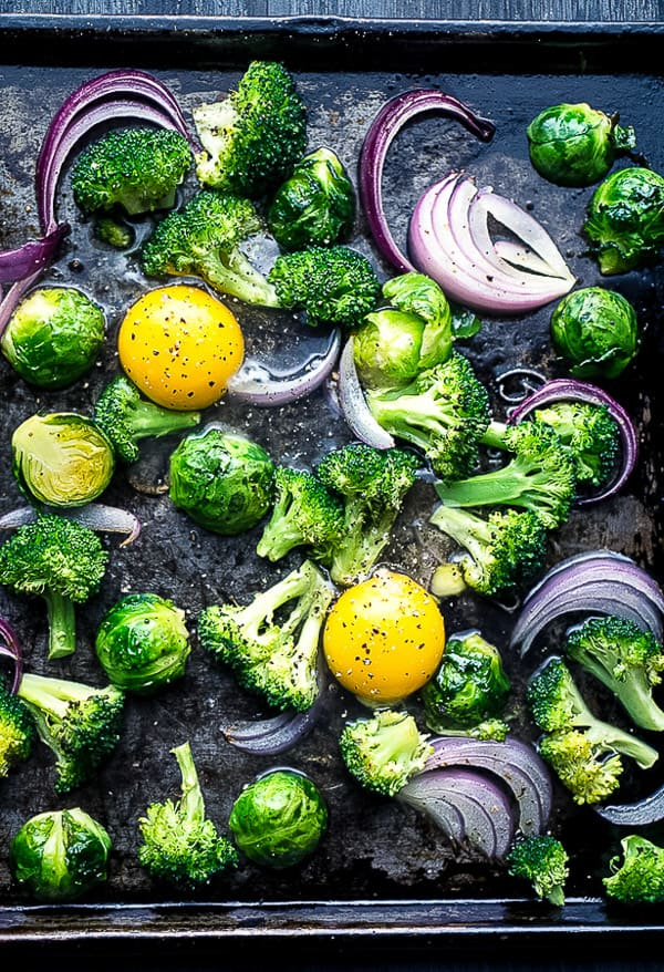 uncooked eggs, broccoli, Brussels sprouts, and red onion on black sheet pan