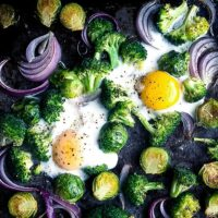 baked eggs, broccoli, Brussels sprouts, and red onion on black sheet pan