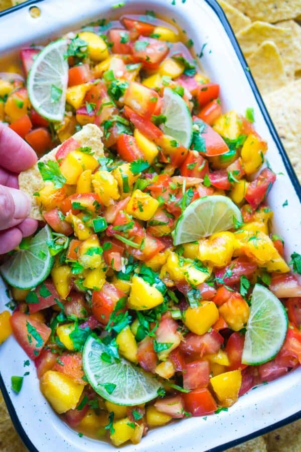 tortilla chip being hand dunked into white bowl of peach salsa