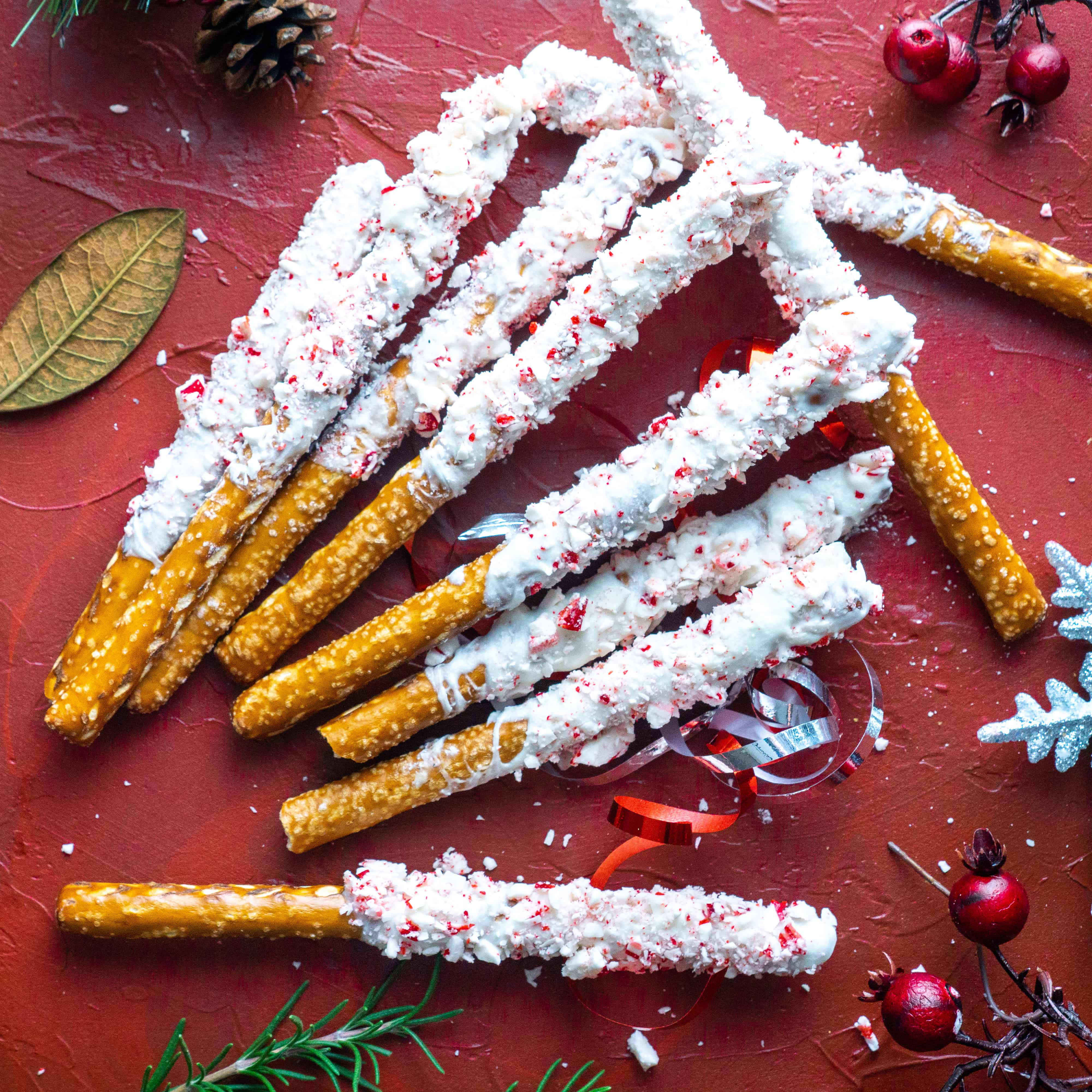 peppermint bark pretzels on red backdrop with holiday decorations