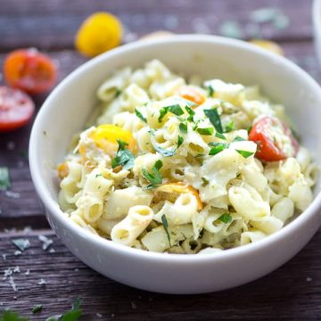 pesto pasta salad in white bowl with cherry tomatoes and parsley on wood background