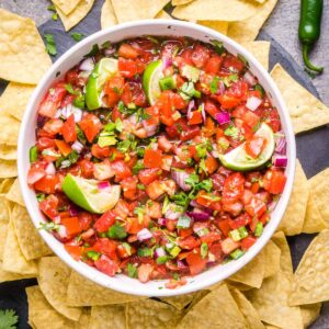 pico de gallo in white serving bowl surrounded by tortilla chips and serrano peppers