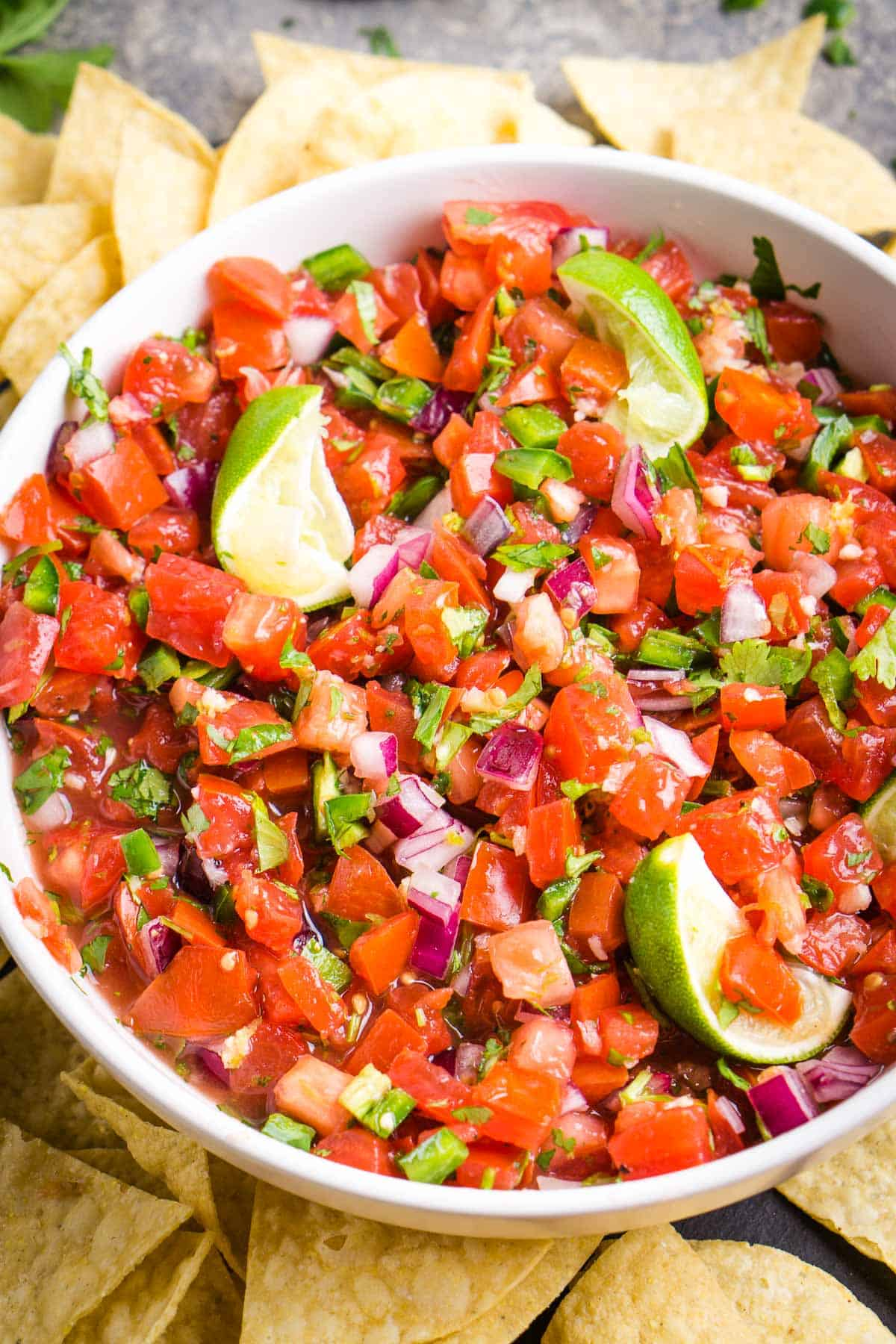 pico de gallo in white serving bowl surrounded by tortilla chips