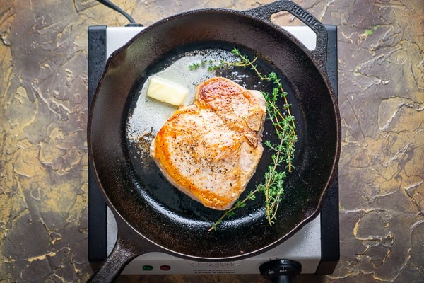 pan seared bone-in pork chop, melted butter, and thyme sprigs in cast iron skillet on electric burner