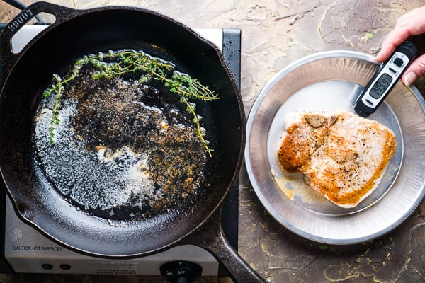 Meat thermometer inserted in pan fried pork chop next to iron skillet on electric burner