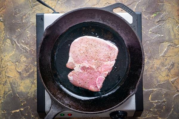 uncooked bone-in pork chop in cast iron skillet on electric burner
