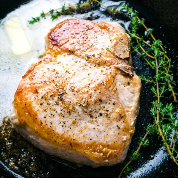 pan seared cast iron skillet pork chop with melted butter and thyme sprigs