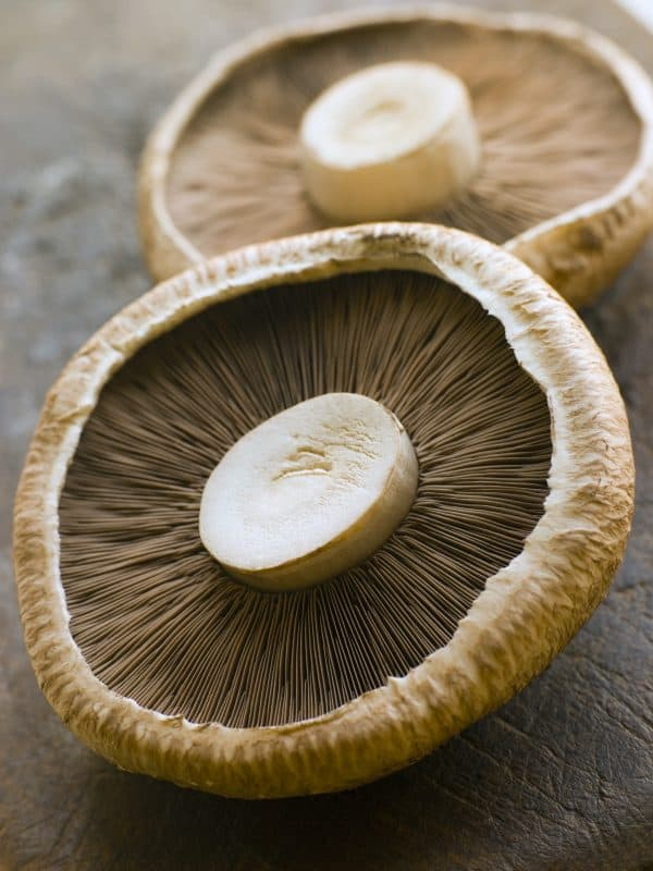 two uncooked portobello mushrooms laying on brown surface showing gills and stem