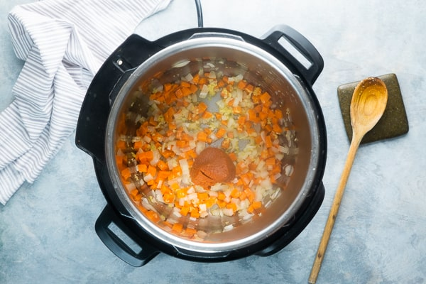 wood spoon stirring pumpkin curry ingredients in the Instant Pot