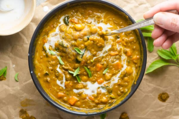 pumpkin curry in black bowl with spoon