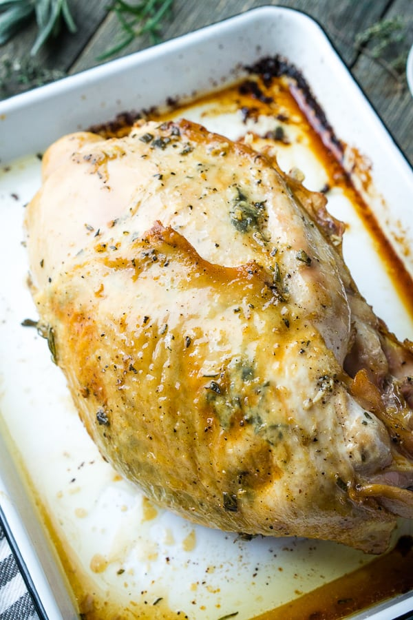 whole roast turkey breast on white tray on gray wooden table surface