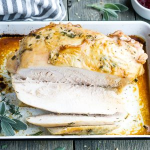 carved roast turkey breast on white baking pan with grey and white towel on gray wooden table surface