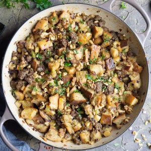 sausage stuffing in skillet with scattered parsley, walnuts, and blue linen