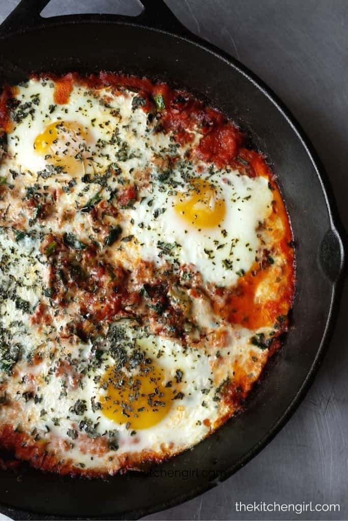 shakshuka in black skillet on gray background
