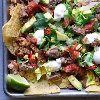 Cadillac nachos!! Made with steak, rice, beans, cheese, lettuce, avocado, cilantro, and peppers! Sheet Pan Steak Salad Nachos on thekitchengirl.com #cincodemayo #sheetpanmeal #sheetpannachos #healthynachos #healthymexican #gameday #glutenfree #nachos #tacosalad #filetmignon