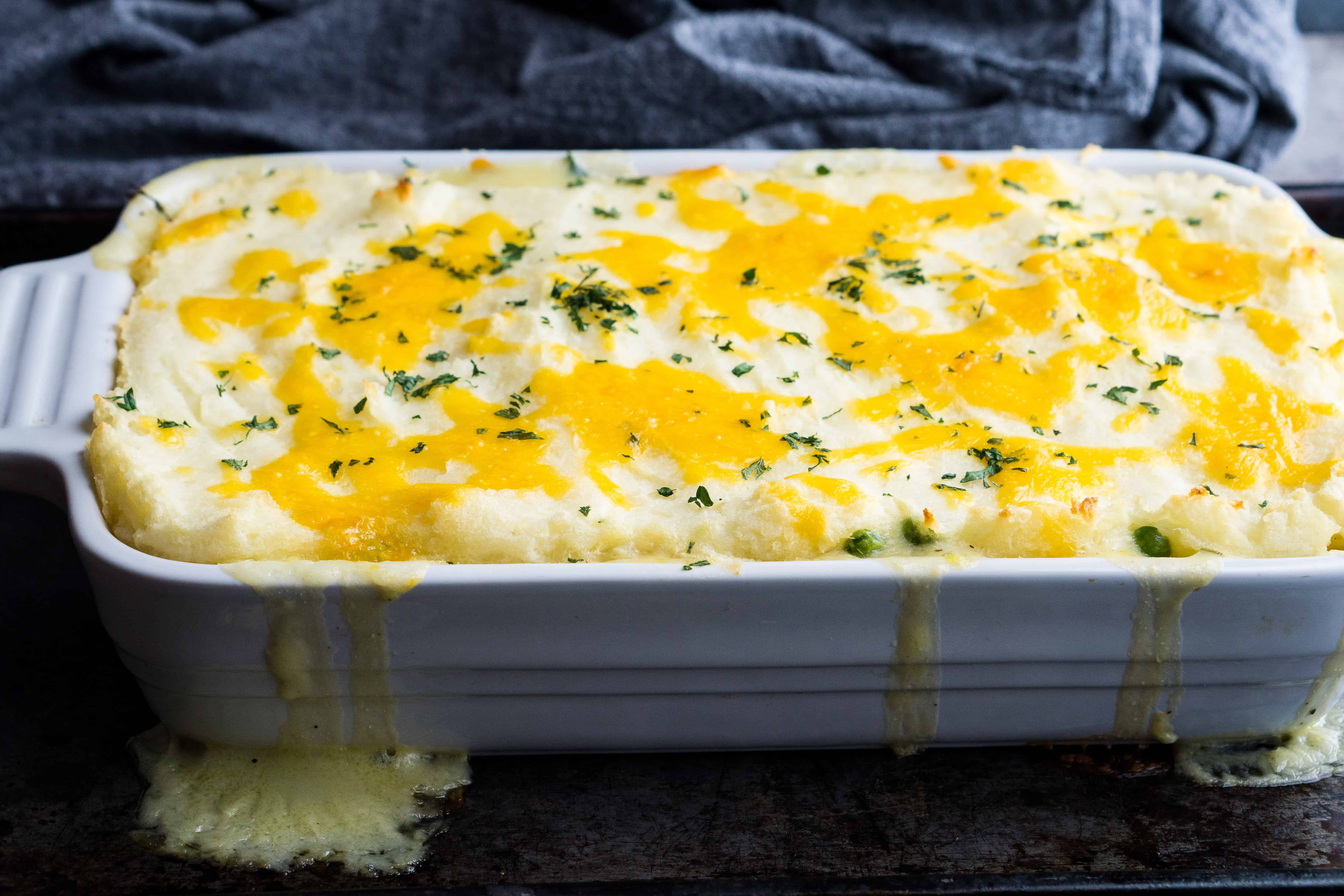 Shepherd's pie in white ceramic baking dish with cheese dripping down the sides