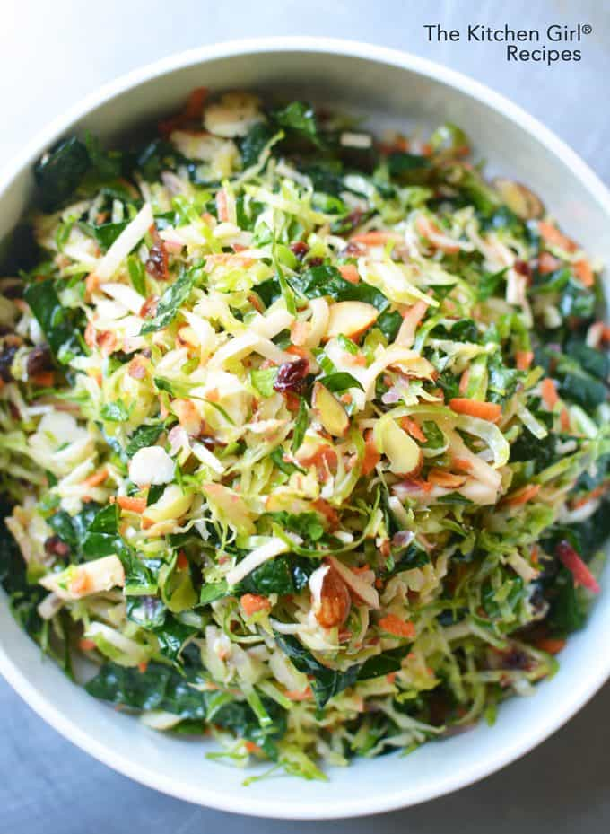 Make 'em love Brussels sprouts! This Apple Cranberry Shredded Brussels Sprout Slaw has kale, almonds, and cranberries in a cider vinaigrette. thekitchengirl.com #brusselsproutsalad #healthyholidayrecipe #cranberryrecipes #holidaysalad