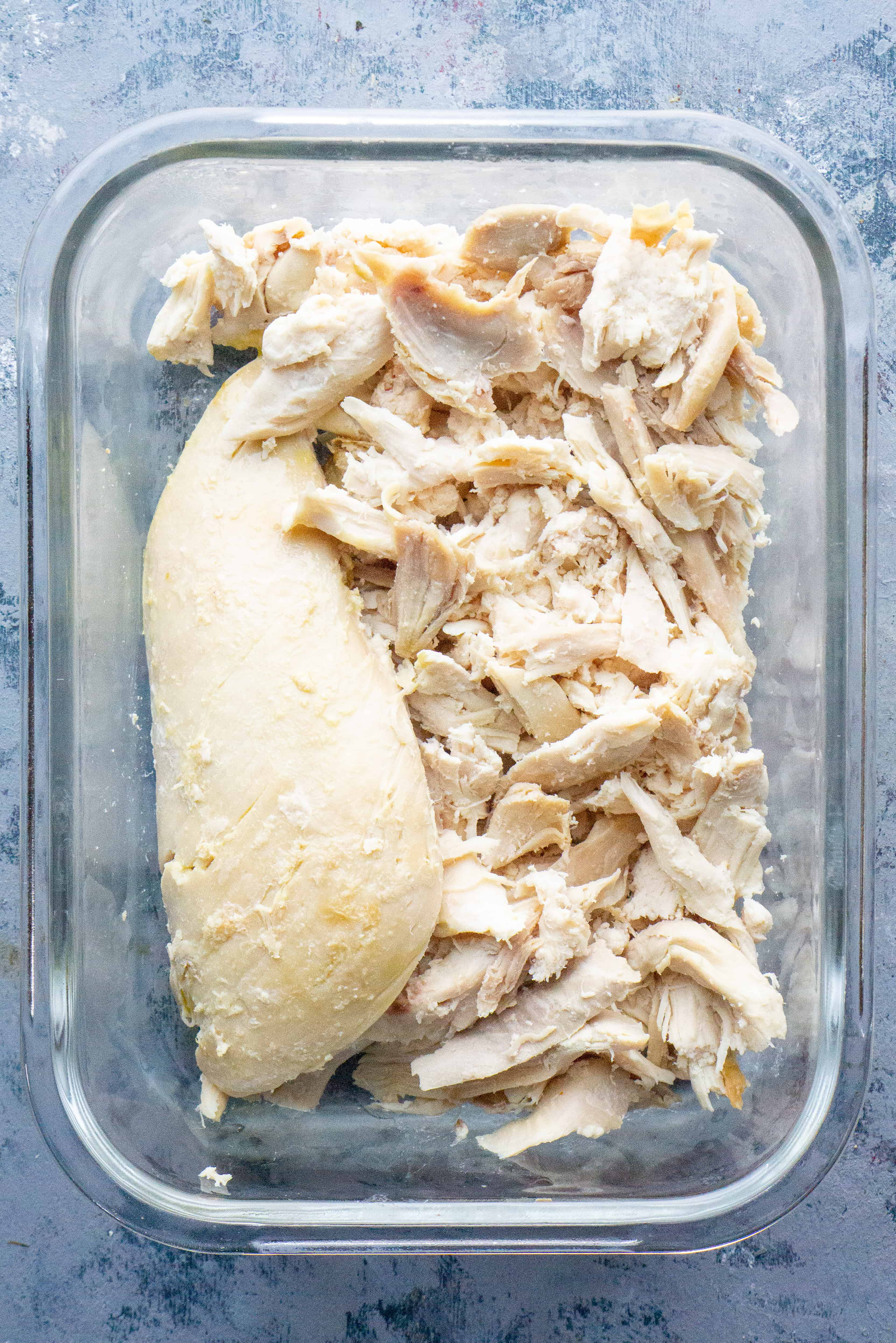 shredded chicken breast or turkey breast in glass meal prep container on grey background