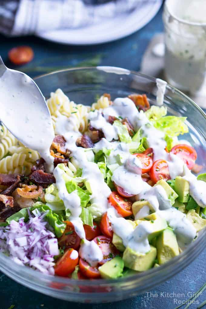 blt pasta salad with spoon drizzling ranch dressing in glass bowl on blue surface with plates, napkin, and ranch dressing in a jar