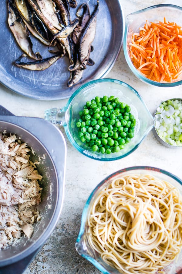overhead view of tuna pasta ingredients: portobello mushrooms, shredded carrots, sweet peas, green onions, tuna, cooked pasta noodles