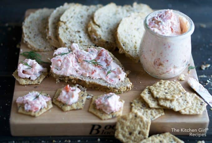 salmon dip in glass jar on cutting board with sliced bread and crackers