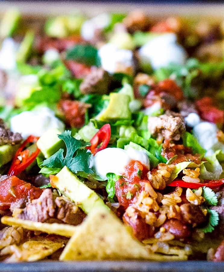 close up of nachos supreme on sheet pan