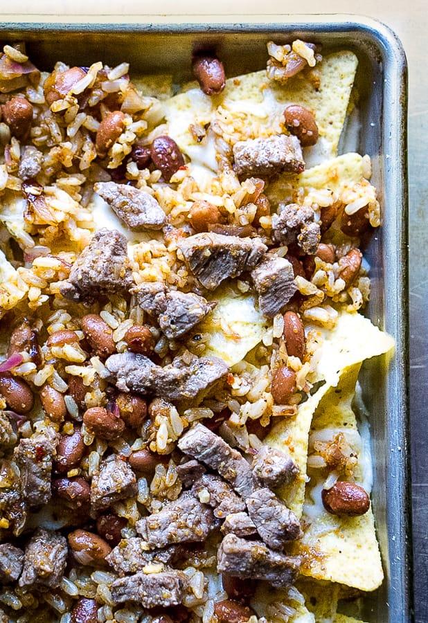 tortilla chips, steak, and beans on sheet pan